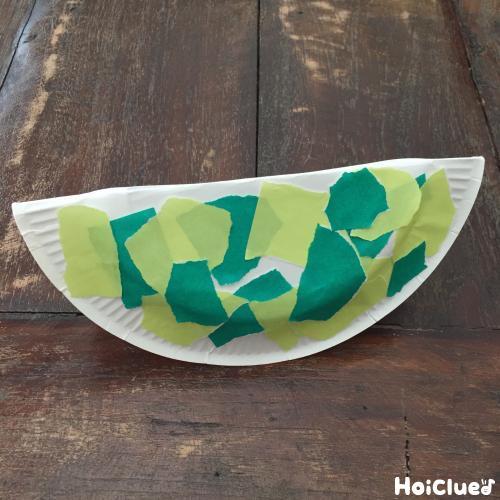 紙皿を半分に折りやぶいた折り紙を貼り付けた写真