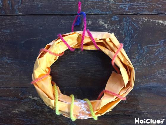 紙を捻って輪を作り毛糸で縛っている写真