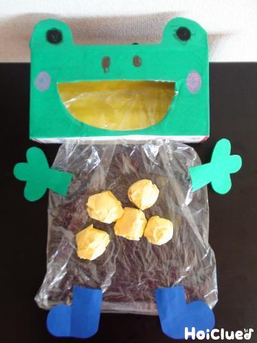 ビニール袋に手足をつけたカエルと玉の写真