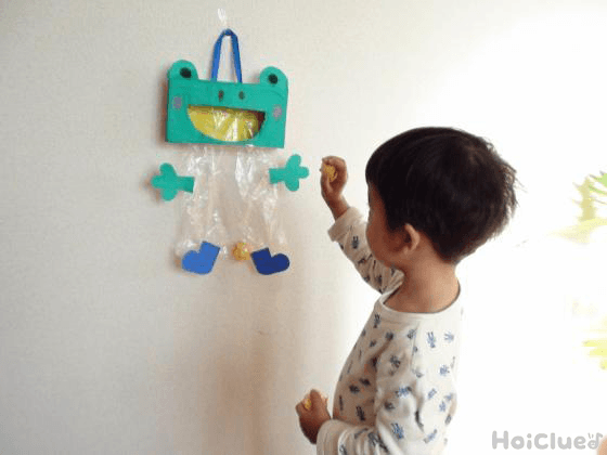 カエルを壁に掛けて玉入れしている様子