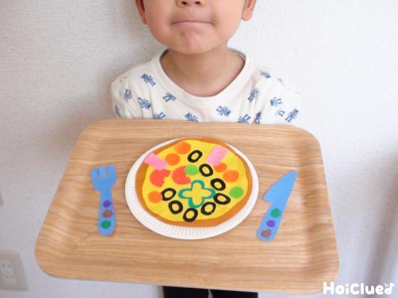 おぼんに乗せたたピザを持つ子どもの写真