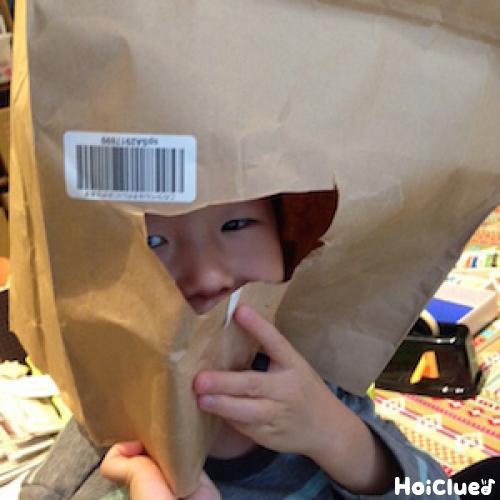 顔部分をくり抜いた紙袋をかぶる子どもの写真
