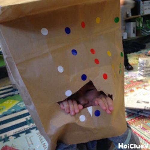 丸シールを貼った紙袋をかぶる子どもの写真