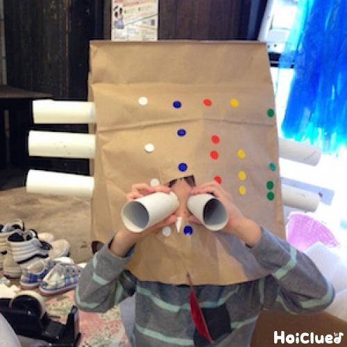 紙袋の側面に3本づつトイレットペーパーの芯を貼り、2本の芯を双眼鏡のようにのぞく子どもの様子