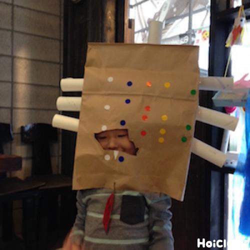 頭部分にもトイレットペーパーの芯を付けた紙袋をかぶる子どもの写真