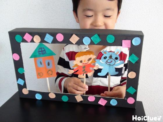 空き箱で作った枠のなかで人形を動かしている写真