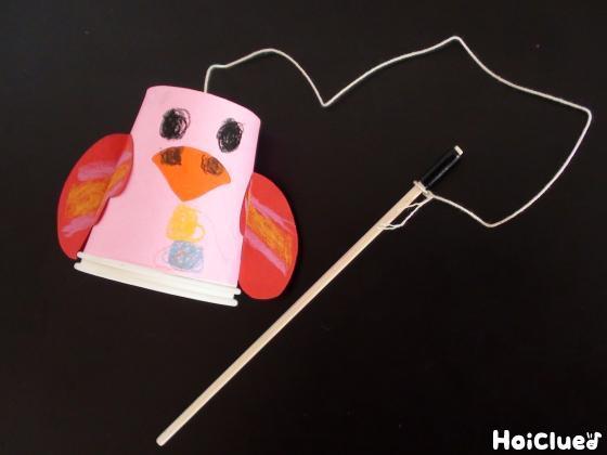 紙コップの鳥を割り箸に留める様子