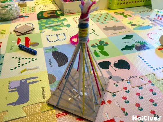 四角いダンボールに格子状に毛糸を巻き付けテント型にした様子