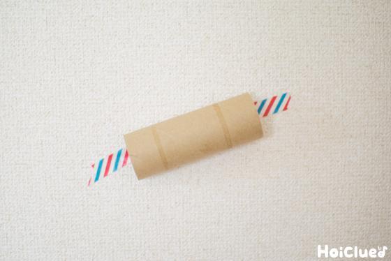 トイレットペーパーの芯をマスキングテープで壁に貼り付けた写真