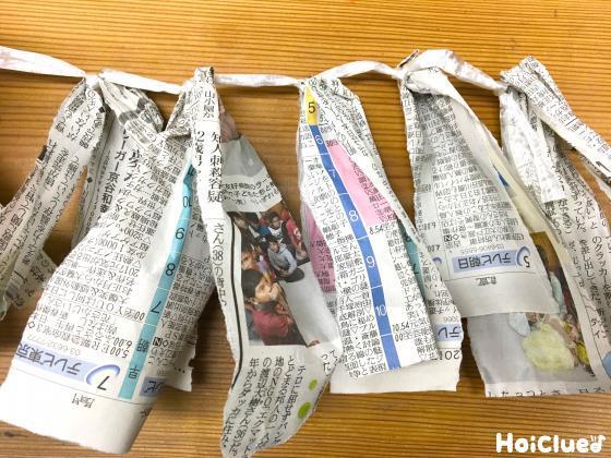 細長い新聞紙を紐に付けた写真
