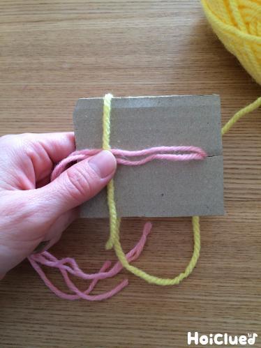厚紙に毛糸を巻きつけようとしている写真