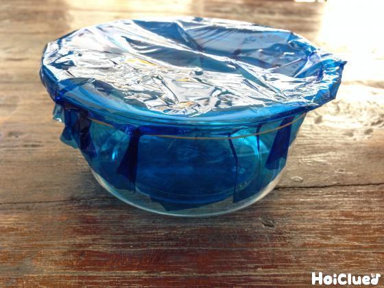 透明な空き容器に青いカラーセロファンをかぶせている写真