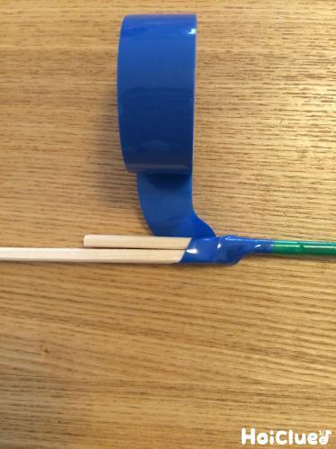 割り箸をビニールテープで繋ぎ合わせる様子