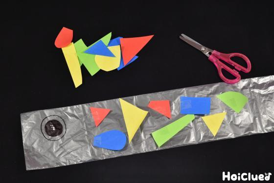 うろこを折り紙でつくり貼り付けている写真