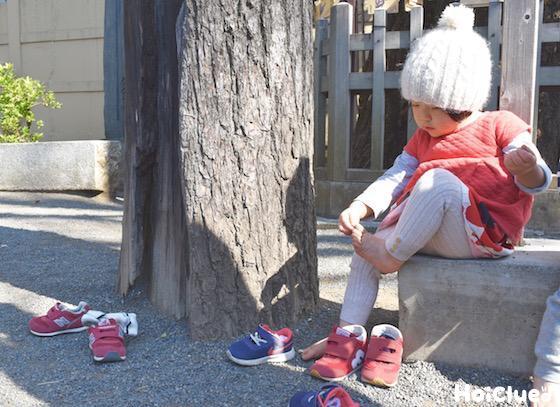 石に座り足を触っている子どもの様子