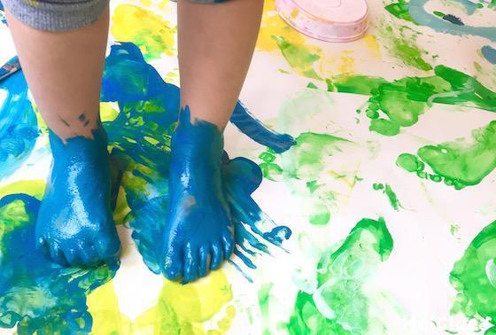 絵の具をつけた足で紙の上に立つ子どもの写真