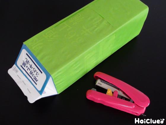 牛乳パックの口をホチキスでとめ黄緑の折り紙を貼り付けた写真
