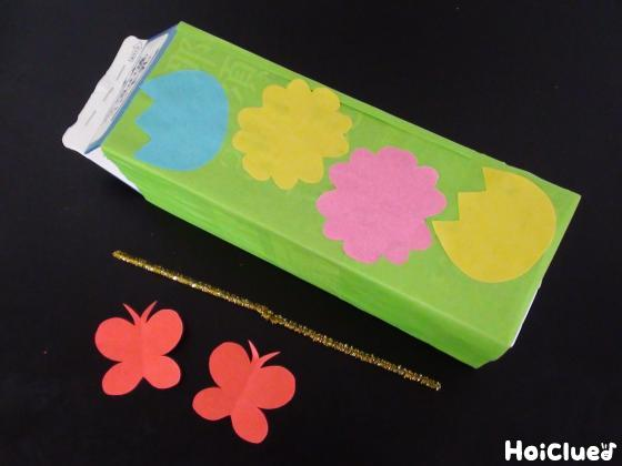 折り紙で花を貼り付けた牛乳パックとモールと折り紙のちょうちょの写真