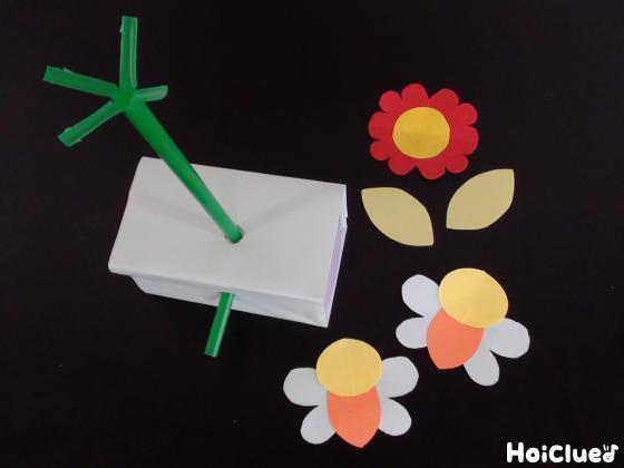 ストローを刺した空き箱と画用紙で作ったお花とミツバチの写真