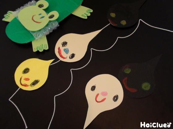 色画用紙で作ったおたまじゃくしをタコ糸に繋げスリッパに貼る様子