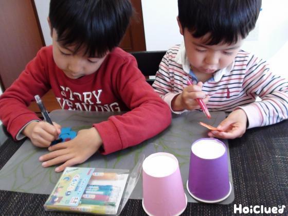 動物の顔と紙コップに絵を描く子どもたち