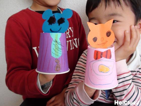 開けた穴に動物の顔をさした紙コップを持つ子どもたち