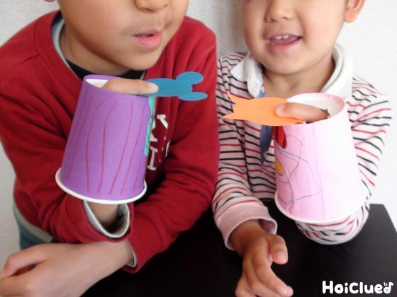 完成した人形をおじきさせて遊ぶ子どもたち