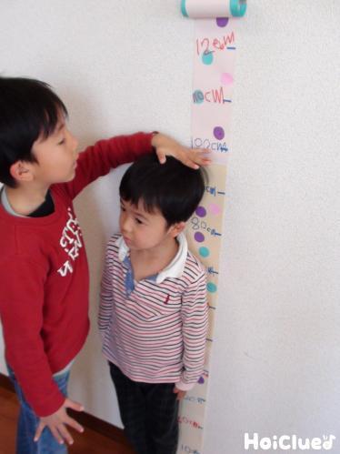 子どもが自分たちで身長を測っている写真