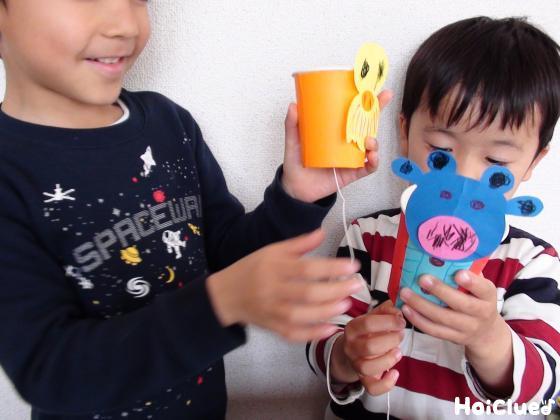 紙コップの鳥とカバを手に持ち底のタコ糸を引っ張る子どもたちの様子