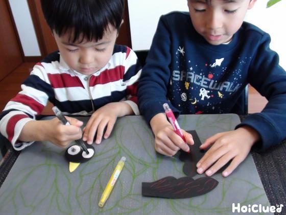 色画用紙で作ったカラスの顔と羽に模樣を描く子どもたち様子