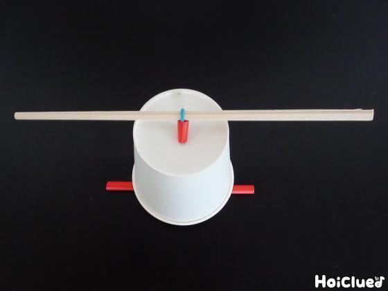 紙コップの底に輪ゴムをとおして両側を割り箸とストローで留めている写真