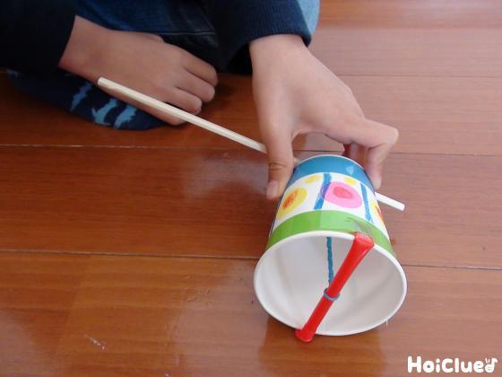 紙コップを床に置き遊ぶ様子