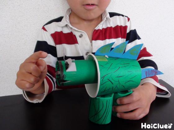 完成した恐竜の頭を指で揺らす子どもの様子