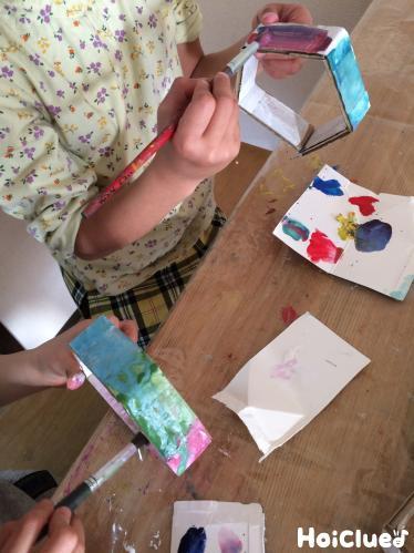 五角形のダンボールに絵の具で色付けする様子