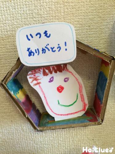 五角形のダンボールの中にメッセージを貼り付けた写真