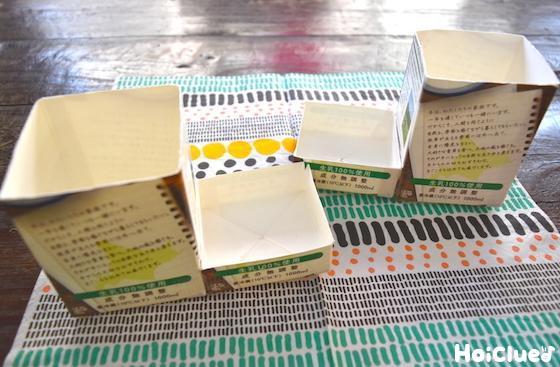 上部分を切り取った高さの違う2個の牛乳パックを繋ぎ合わせた写真