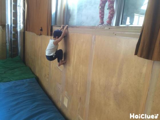 壁をよじ登る子どもの写真