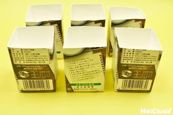 上部分を切り取った6個の牛乳パックの写真