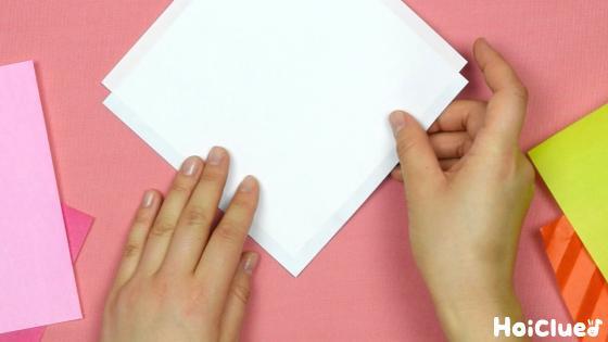 色の違う2枚の折り紙を裏向きにし少しずらして重ねた写真