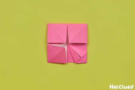 4つある四角のうち1つを、中心部分を軸にして三角に折る様子