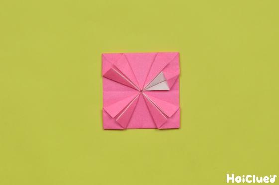 折った三角の部分を袋状に開いてつぶすように折った様子