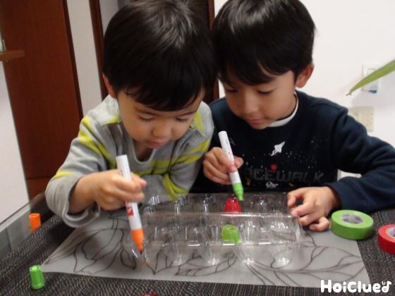 油性ペンで卵パックに絵を描く子どもたちの様子
