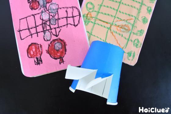 折り曲げた紙コップと模様を描いたダンボール