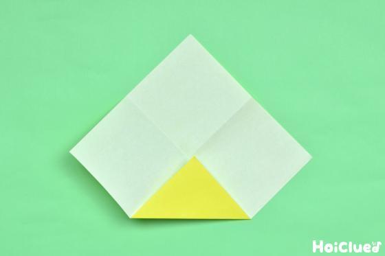 折り跡のついた折り紙を角から中心に三角に折った写真