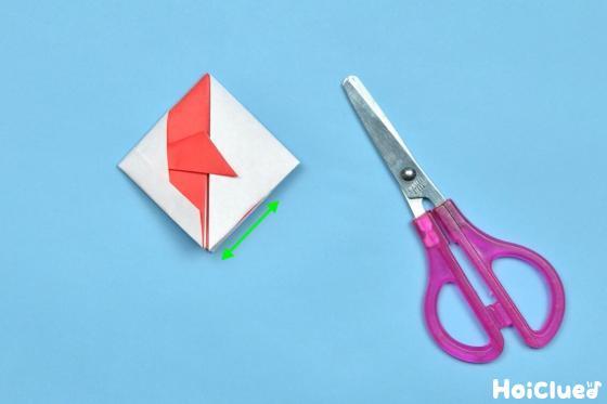 矢印の部分に切り込みを入れた折り紙とハサミの写真