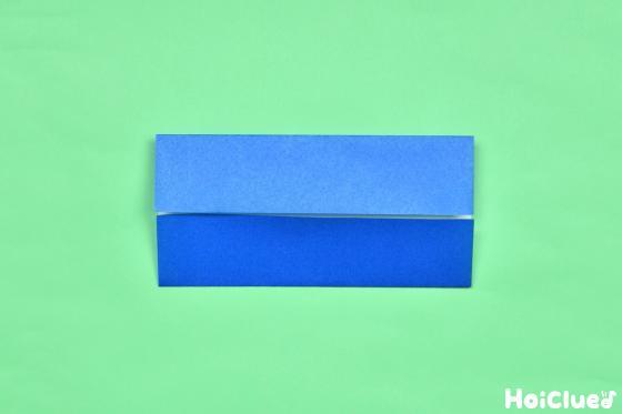 折り目の付いた折り紙を両側から中心に折り長方形にした写真