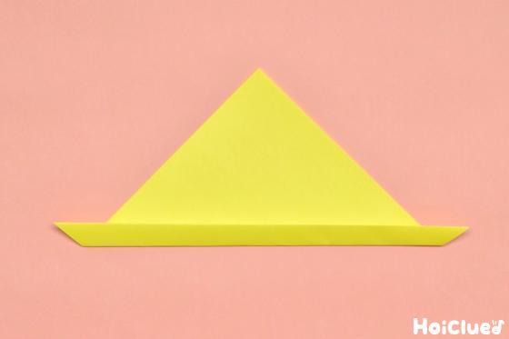 三角に折った折り紙の底辺を少し折り返した写真