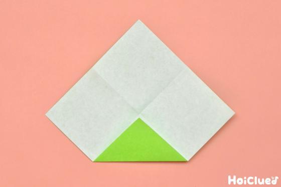 一度開いて折り紙を角から中心に三角に折った写真