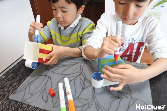 油性ペンでカップに模樣を描く子どもたち