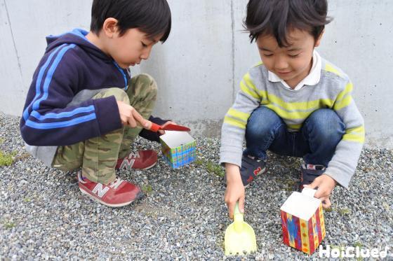 スコップで砂利を入れて遊ぶ子どもたちの様子